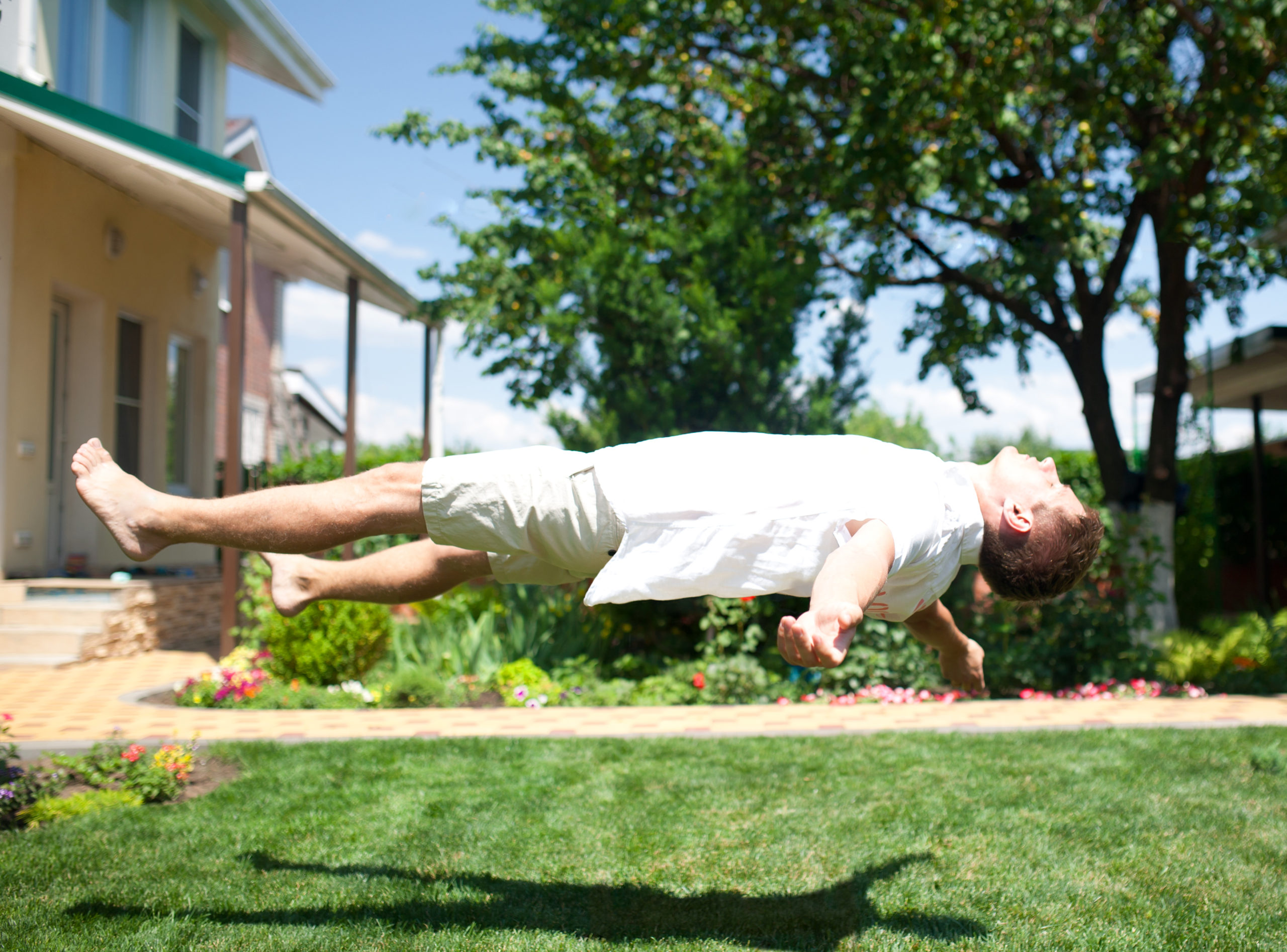 Young man flying or levitating over grass in the backyard, holiday concept