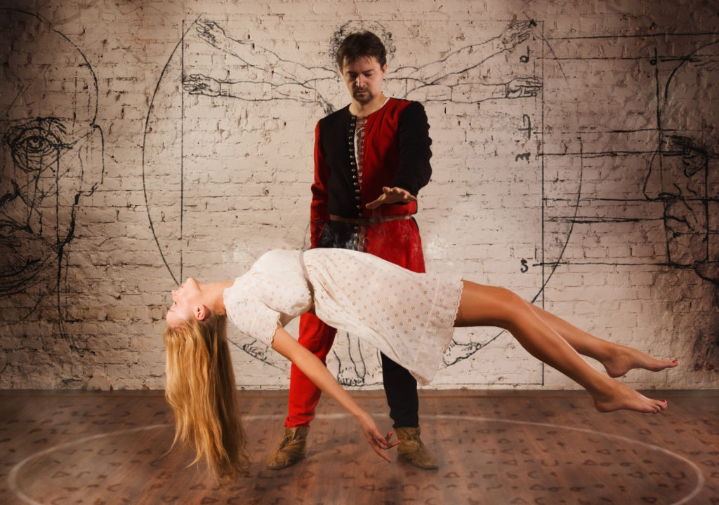 Magic moment - man in medieval suit performing magically levitating his girl assistant