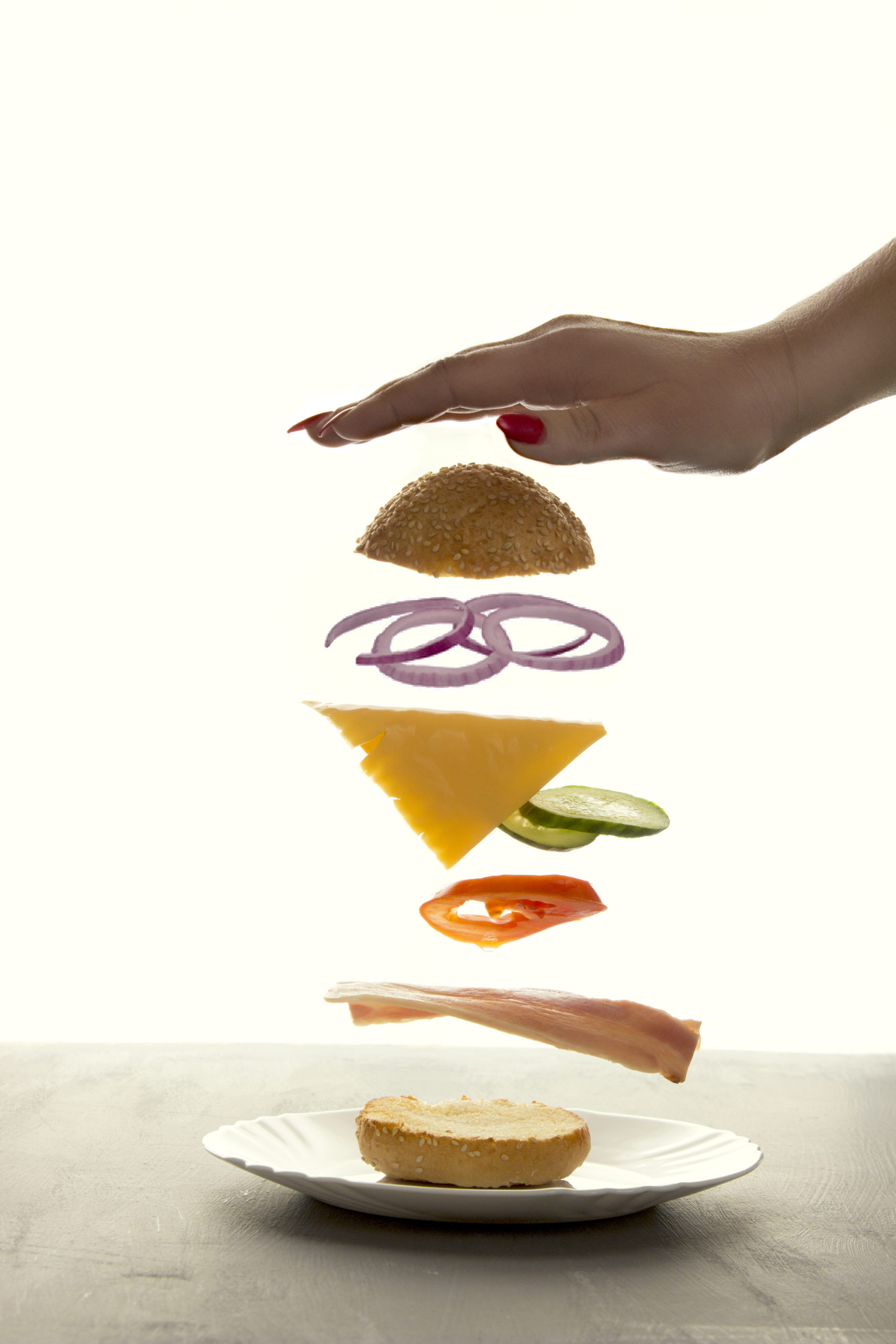 Sandwich floating in the air on a white background. The sandwich rises behind the woman's hand, the power of levitation.